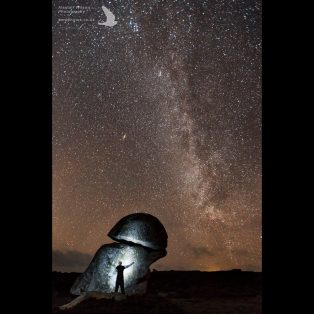 Silhouette of the photographer against the 'Punchbowl' St Agnes, with the Milky way above
