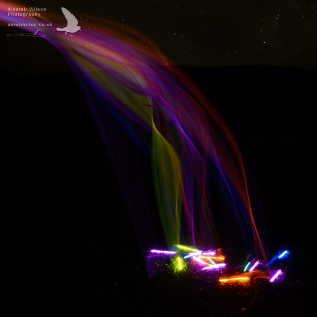 Glow sticks falling like a rainbow waterfall